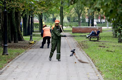 Janitors sweep the sidewalks in the park Stock Images