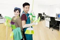 Janitors trzymają cleaning wyposażenie w biurze Obrazy Royalty Free