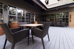 Jantando a tabela de madeira com cadeiras de vime fora Foto de Stock