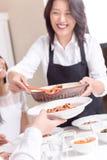 Jantar asiático do serviço da mamã em casa Imagem de Stock
