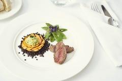 jantar com carne em uma placa de jantar branca pura com pão, água Fotos de Stock