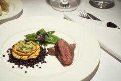 jantar com carne em uma placa de jantar branca pura com pão, água Fotos de Stock Royalty Free