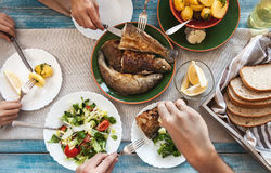 Jantar com peixes fritados, batatas e salada fresca Imagem de Stock Royalty Free