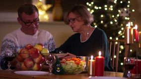 Jantar da família no Natal O marido e a esposa idosos estão sentando-se na tabela na ação de graças A mulher põe o alimento sobre filme