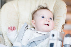 Jantar de espera do bebê doce em uma cadeira alta Imagem de Stock