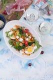 Jantar do feriado Salada com vegetais, camarões, ovo Dois vidros do vinho Tabela clara imagem de stock