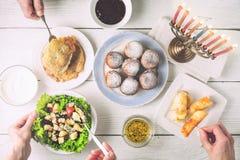 Jantar do Hanukkah com os pratos tradicionais horizontais imagem de stock