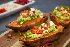 Jantar saudável - as batatas doces cozidas serviram com guacamole, queijo de feta e romã fotos de stock royalty free
