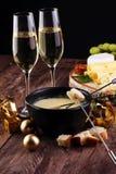 Jantar suíço gourmet do fondue em uma noite do inverno com queijos sortidos em uma placa ao lado de um potenciômetro caloroso do  Foto de Stock
