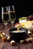 Jantar suíço gourmet do fondue em uma noite do inverno com queijos sortidos em uma placa ao lado de um potenciômetro caloroso do  Imagem de Stock