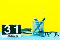 31. Januar Tag 31 von Januar-Monat, Kalender auf gelbem Hintergrund mit Büroartikel Blume im Schnee Lizenzfreie Stockbilder