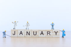 Januar-Wörter mit Miniaturleutearbeitskraft Lizenzfreie Stockfotos