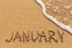 Januari - ord som dras på sandstranden med den mjuka vågen Royaltyfria Bilder