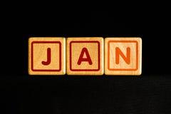 Januari på wood kubik på svart bakgrund royaltyfri bild