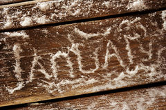 January. Snow letters on a wooden surface Royalty Free Stock Photo