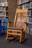 Oak rocking chair in  the middle of a library royalty free stock photography