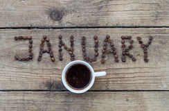 JANUARY coffee beans on wooden background. Cup of coffee on wooden background and January coffee beans Stock Photos