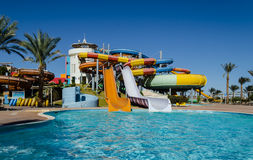 January 2016:  Colorful water slides in the water park, Hurghada. Multicolored, extreme slides for adults, flowing into the pool against the blue sky, Hurghada Royalty Free Stock Image