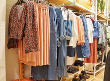 January 2019, Moscow, Russia. women`s clothing on hangers and shelves in the store, coral gamma stock photography