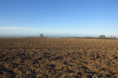 January plow soil. An agricultural landscape with patterns and textures of freshly plowed soil in winter under a clear blue sky on the yorkshire wolds england Royalty Free Stock Photography