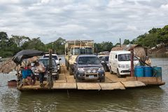 Vehicles are transported across river on small ferry. January 6, 2017 Sayaxche, Guatemala: vehicles are transported across the river with a makeshift private Stock Photography