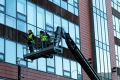 January 29th, 2018, Cork, Ireland - men doing high-rise window cleaning work in the Blackpool Retail Park. With a crane Stock Photos