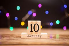 January 10th. Day 10 of January set on wooden calendar on dark background with garland bokeh. Winter time. Holiday Composition. January 10th. Day 10 of January stock photo