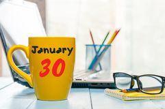 January 30th. Day 30 of month, Calendar on cup morning coffee or tea, white-collar worker workplace background. Winter. At work concept. Empty space for text Royalty Free Stock Photography