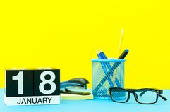 January 18th. Day 18 of january month, calendar on yellow background with office supplies. Winter time.  Stock Photos