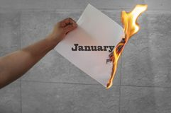 January word text on fire with burning paper. In hands stock photos