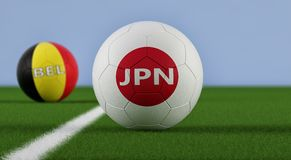 Japão contra Fósforo de futebol de Bélgica - bolas de futebol em cores nacionais de Japão e de Bélgica em um campo de futebol Fotografia de Stock Royalty Free