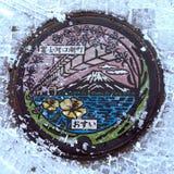 Japan's人孔盖和雪在冬天,日语鞋帮秀丽:Kawaguchiko镇 免版税库存照片
