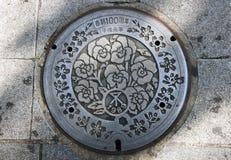 Japan's在边路的人孔盖的秀丽花纹花样 日语:平成100年纪念品  免版税图库摄影