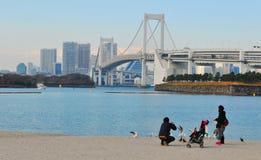Japan. Tokyo, Japan - 2 January, 2012: Japanese family enjoying the view of the Rainbow Bridge in Daiba, Tokyo Stock Photo