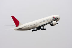 Japan Airlines Boeing 777 toglie. Immagini Stock