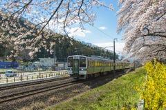 Japan - April 12, 2016: JR trein Sendai langs spoorweg met Duizend Sakura Trees naast Shiroishi-rivier, Sendai in werking dat wor Royalty-vrije Stock Fotografie