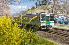 Japan - April 12, 2016: JR trein Sendai langs spoorweg met Duizend Sakura Trees naast Shiroishi-rivier, Sendai in werking dat wor Royalty-vrije Stock Afbeelding
