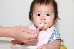 Japan behandla som ett barn flickan som att äta behandla som ett barn mat Arkivfoto