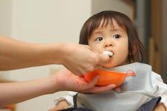 Japan behandla som ett barn flickan som att äta behandla som ett barn mat Arkivbild