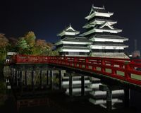 Japan-castle. Donjon of Matsumoto Castle reflected in the moat. A red bridge crosses the moat. The castle dates to the early 16th century and is located in the Stock Photography