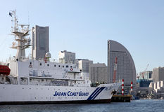 JAPAN COAST GUARD BOAT. A Japan coast Guard boat against a backdrop of some of the most famous landmark buildings in Yokohama in Japan royalty free stock photos