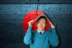 Japan earthquake. Cracked brick wall as Japan flag and asian male with laptop Royalty Free Stock Images