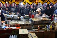 Japan festival food. CHICHIBU, JAPAN - DECEMBER 3, 2016: Vendor prepares street food at Chichibu Night Festival in Japan. Chichibu Yomatsuri festival was added Stock Image