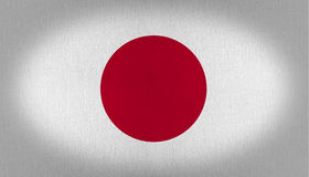 Japan flag. With a big red circle as a representation of the sun in the center of it, over a white back, fabric texture background vignette Royalty Free Stock Photos