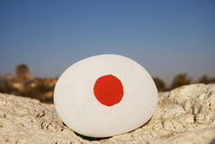 Japan flag colours on a stone. Closeup shot over a stone with the colours of the japan flag over a rock royalty free stock photo