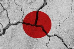 Japan flag on the cracked earth. National flag of Japan. Earthquake or drought concept stock images
