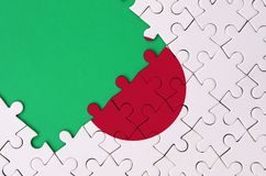 Japan flag is depicted on a completed jigsaw puzzle with free green copy space on the left side.  vector illustration