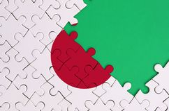Japan flag is depicted on a completed jigsaw puzzle with free green copy space on the right side.  stock photo