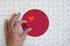 Japan flag is depicted on a puzzle, which the man`s hand completes to fold.  vector illustration