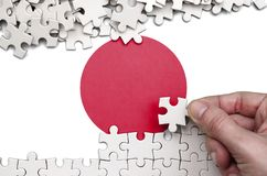 Japan flag is depicted on a table on which the human hand folds a puzzle of white color.  stock image